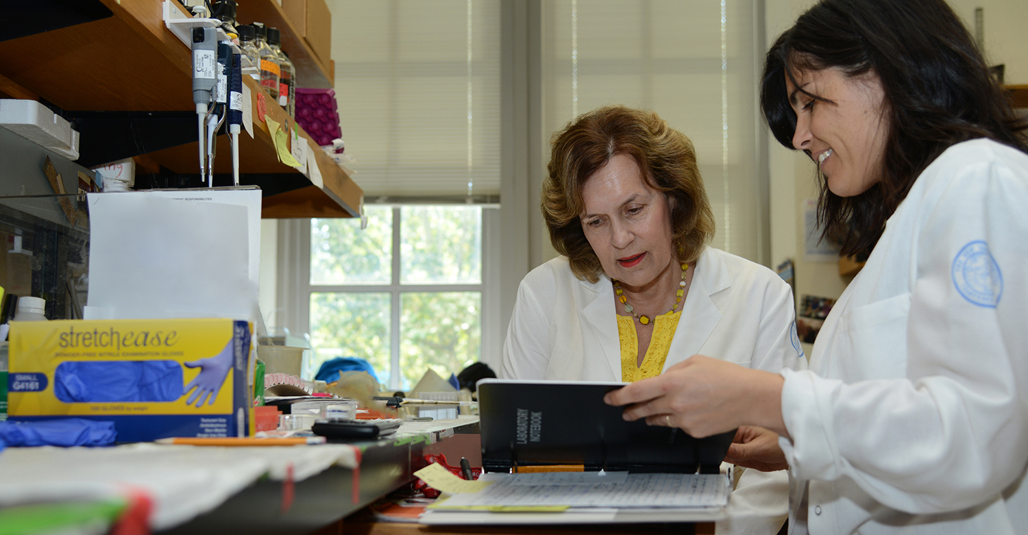 Lorraine Gudas sits with a student, reviewing data from a recent experiment.