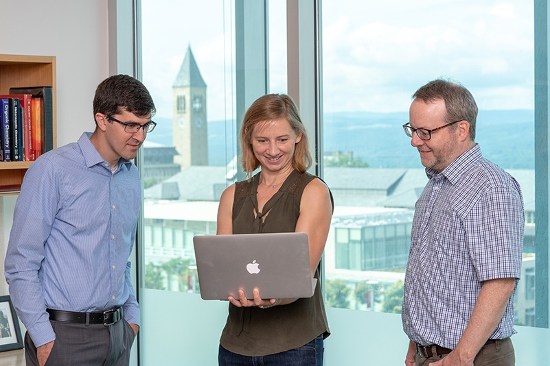 Erin E. Stache, Cornell Presidential Postdoctoral Fellow, with Brett P. Fors and Geoffrey W. Coates, Chemistry and Chemical Biology, looking at a computer.