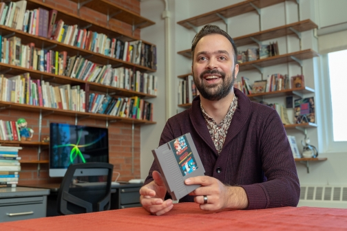 Andew Campana, a Cornell Presidential Postdoctoral Fellow, smiles and holds a video game cartridge.