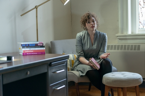 Jessica Cooper sits beside desk and talks.