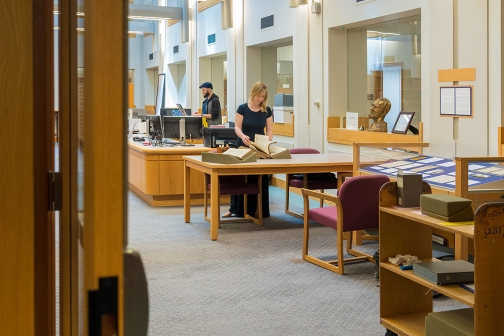 Mackenzie Cooley, a Cornell Presidential Postdoctoral Fellow, examines a large book in a library reading room.