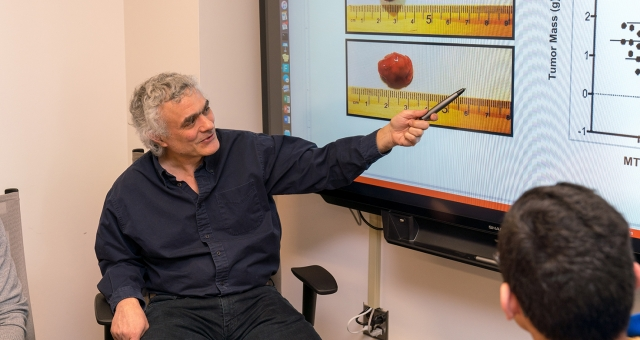 John Schimenti pointing at a Powerpoint presentation