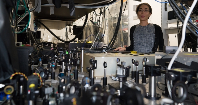 Nozomi Nishimura standing by optical devices in her lab.